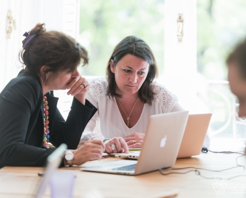 Photo de deux personnes en train de travailler sur leurs ordinateurs